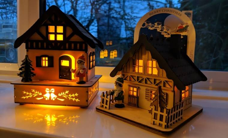 Image of two LED lit wooden houses on windowsill