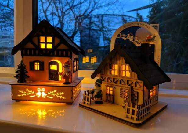 Larger Image of two LED lit wooden houses on windowsill