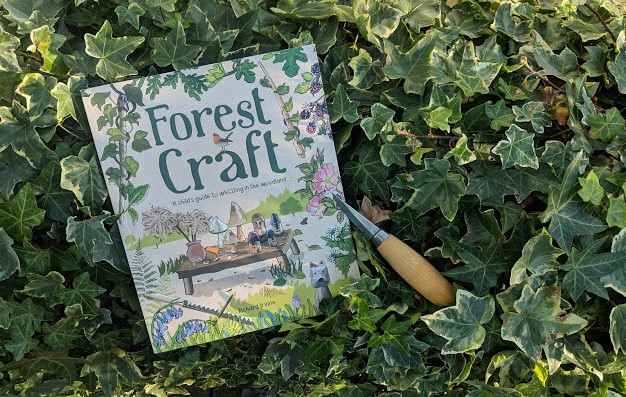 Image of book titled Forest Craft by Richard Irvine displayed on ivy with whittling knife on top