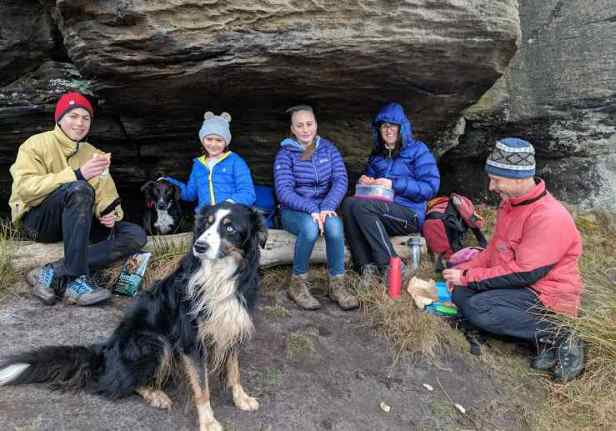 Image of family group of five people and two dogs eating picnic sitting under rocky outcrop