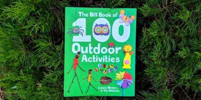 Image of front cover of green book titled The Big Book of 100 Outdoor Activities displayed on evergreen foliage