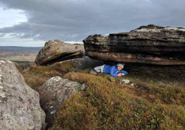 Image of girl in blue jacket lying in rocky crevice on high hill crags with views behind