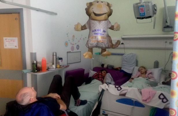Image of man, woman and child asleep in separate beds on childrens cancer hospital ward