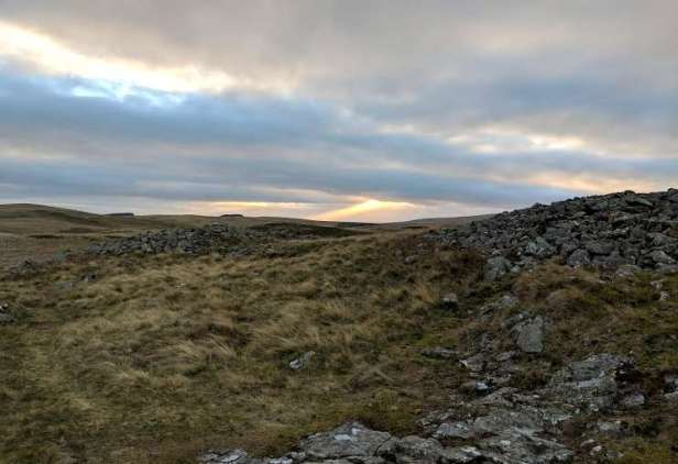 Image of sun ray bursting through grey clouds in distance at top of rocky grass hilltop
