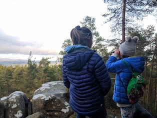 Image of two girls looking over distant view using monocular