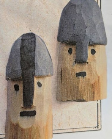 Image of two wooden carvings in shape of face with Norman helmet on head