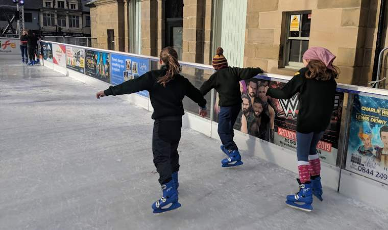 Image of 3 girls in dark green scout uniforms ice skating outdoors 2