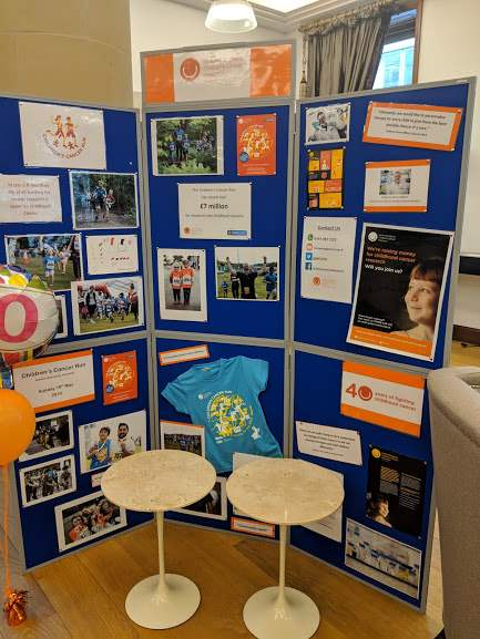 Image of display board with photos and A4 sheets detailing info on children's cancer research in the UK