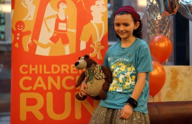 Image of girl wearing blue T-shirt, silver sparkly skirt and headband holding teddy in front of orange NECCR Children's Cancer Run banner