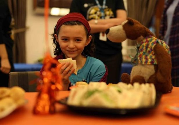 Image of smiling girl in blue T-shirt sat eating at a table with a teddy looking at her sandwich