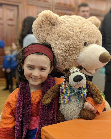 Image of smiling girl in rainbow coloured jumper holding teddy sat next to giant teddy bigger than her
