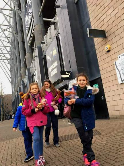 Image of three girls and a woman outside Newcastle United Football Club's official store at St James' Park