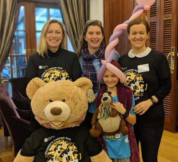 Image of three women and a girl with balloon sculpture on head, standing smiling with giant teddy in black T-shirt