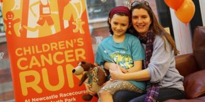Image of woman with girl sitting on lap on settee in front of orange Children's Cancer Run banner