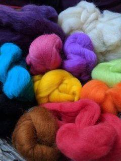 Image close up of brightly coloured rolls of felting wool roving in pink, purple, blue, yellow, brown, green, orange, cream and black