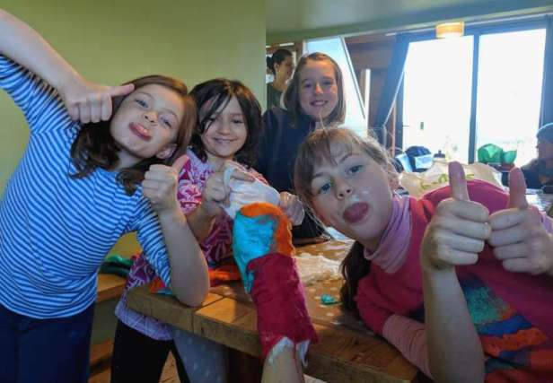 Image of four girls with thumbs up sticking tongues out showing a felted foot in middle that they've wrapped in multi coloured felted wool squares
