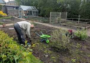 Image of woman and girl digging weeds from soil in allotment vegetable patch