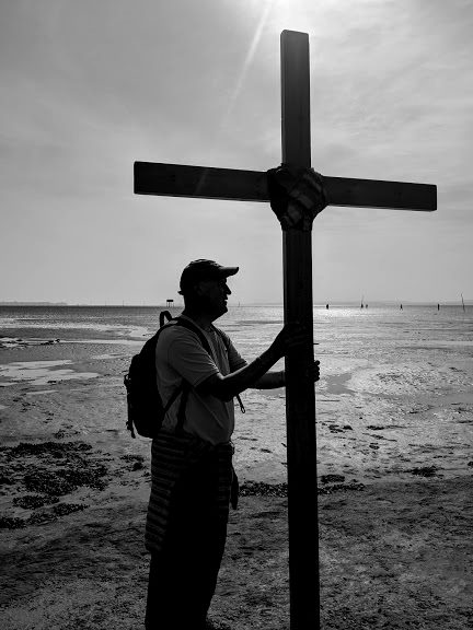Black and white silhouette image of man holding cruxifixion cross at Holy Island causeway with mudflats and sun behind