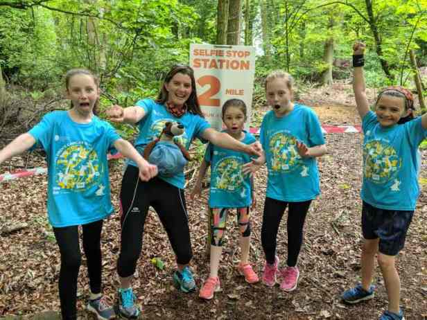 Image of 4 girls and a womand in blue Childrens Cancer Run T-shirts at 2-mile selfie stop point in woods