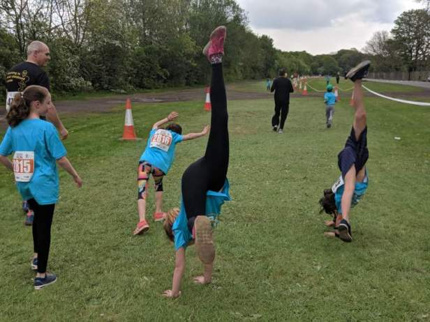 Image of 4 girls cartwheeling on grass running racetrack with trees either side