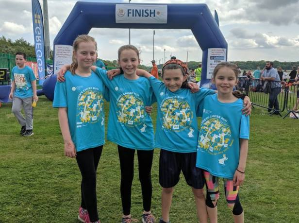 Image of 4 girls in blue T-shirts at finish line of Childrens Cancer Run
