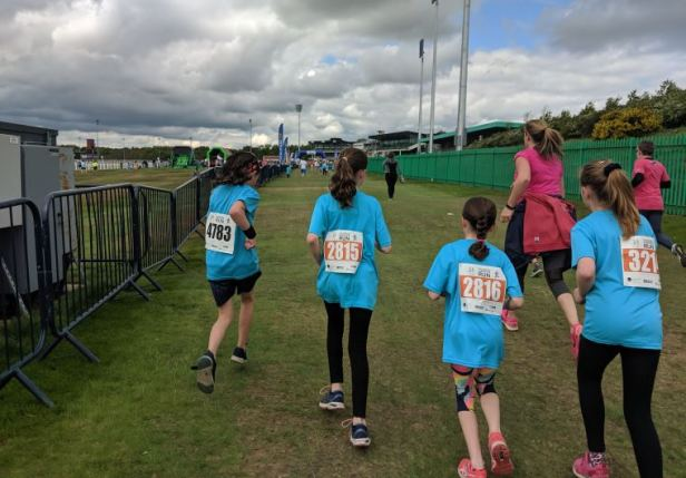 Image of 4 girls in blue Childrens Cancer Run T-shirts running beside metal railing with finish line in background