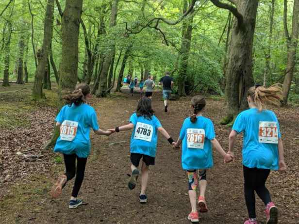 Image of 4 girls in blue race T-shirts holding hands running through woods with other runners in front