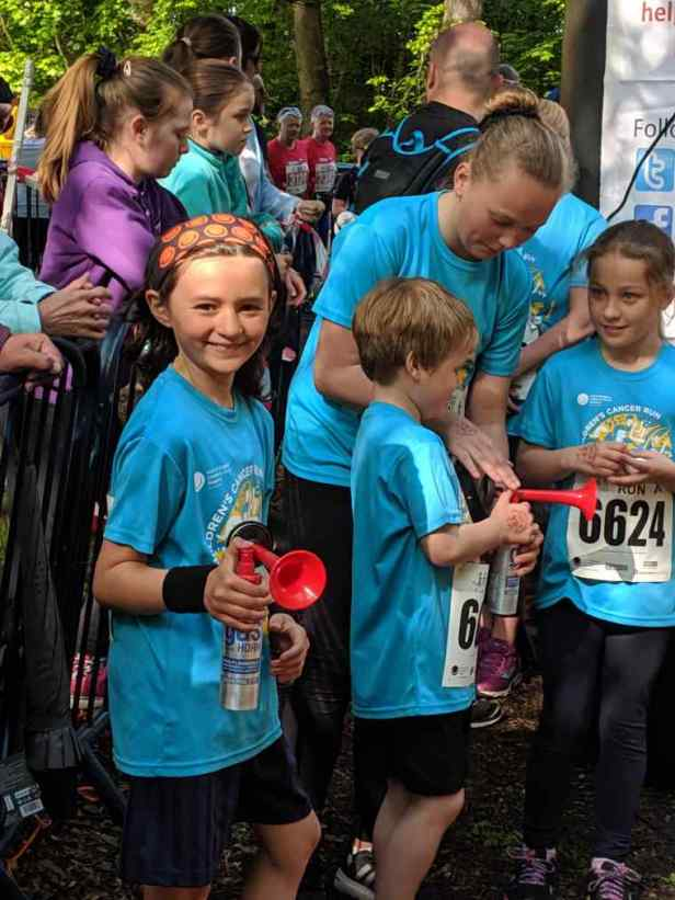 Image of children in blue T-shirts with girl holidng red air horn to start charity run