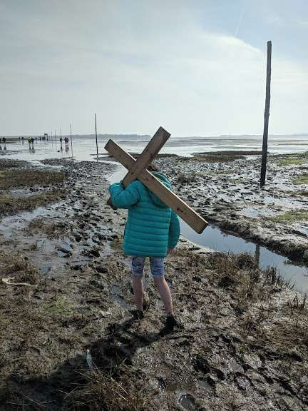 Image of girl in green jacket with bare feet and rolled up trousers walking in mud carrying wooden cross over shoulder on causeway crossing pilgrimage to Holy Island