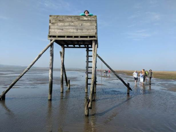 Image of girl on top of wooden refuge hut on causeway crossing to Holy Island