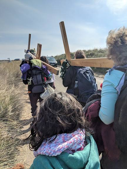 Image of girl with curly hair walking beside people carrying wooden crosses
