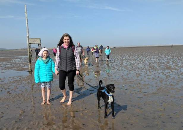 Image of girl, woman and black dog on lead walking barefoot on mud flats in sunshine on Holy Island causeway