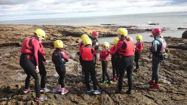 Image of group of children and adults standing on rocks at sea edge wearing red wetsuits and yellow helmets