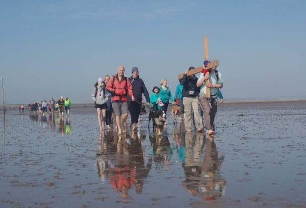 Image of group of people and dogs carrying wooden cross over mudflats with bare feet