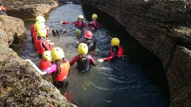Image of group of people wearing red wetsuits and yellow helmets floating in large sea rock pool