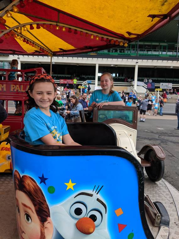 Image of two girls in blue T-shirts having fun on a fairground teacup ride