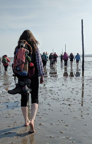 Image of woman from behind with bare feet carrying back pack and walking boots along mud flats at Holy Island Causeway with people and wooden waymarker posts