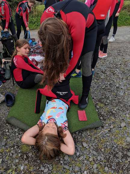 Image of woman helping child put on wetsuit