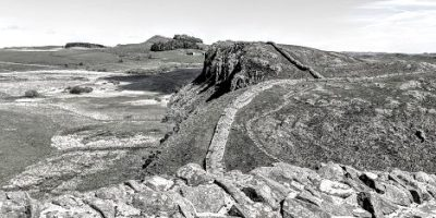 Image in black and white of dry stone wall in foreground with long stretch of Hadrian's Wall in distance along ridge of land