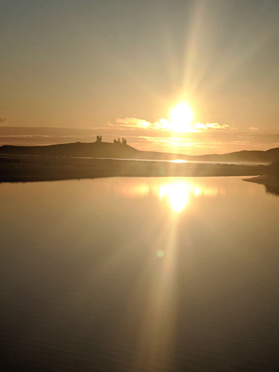 Image of morning midwinter sunshine glare and reflection in water with silhouette of headland and castle in distance