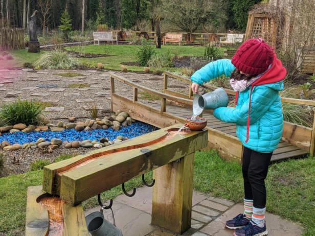 Image of child in red hat, green coat and black leggings pouring water from a jug into a sensory garden water feature