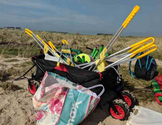 Black beach trolley containing litter pickers and beach school equipment