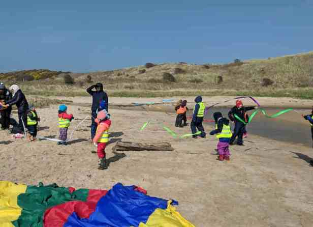 Children in outdoor gear on sandy beach playing with ribbons on sticks at beach school
