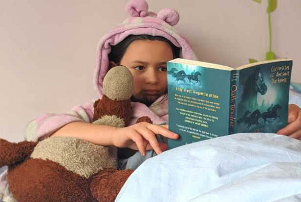 Image of child wearing dressing gown with ears reading paperback adventure story with teddy bear