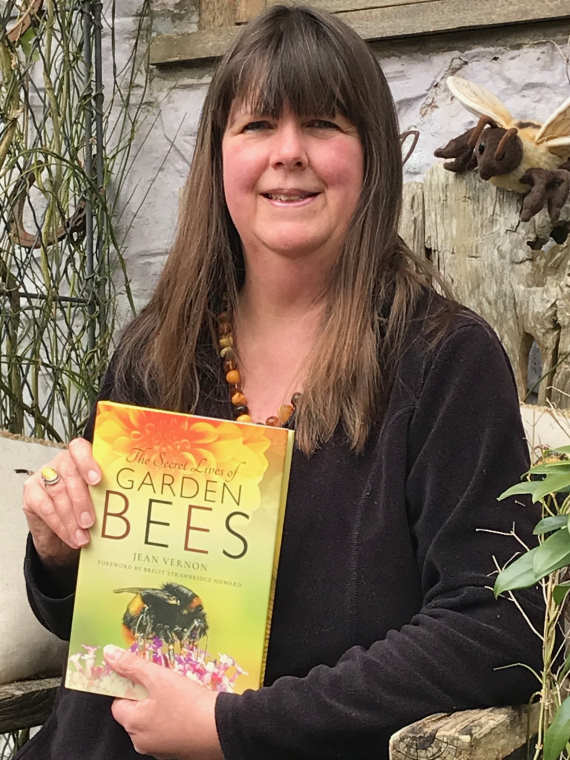 Portrait of author Jean Vernon sitting on bench with her book The Secret Lives of Garden Bees