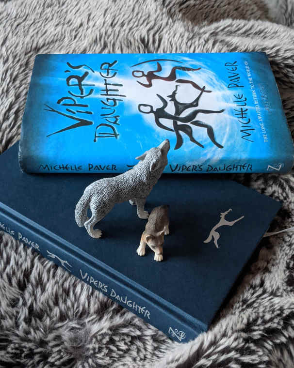 Blue front cover of Viper's Daughter book by Michelle Paver on top of navy inner book with silver design and model wolf standing over