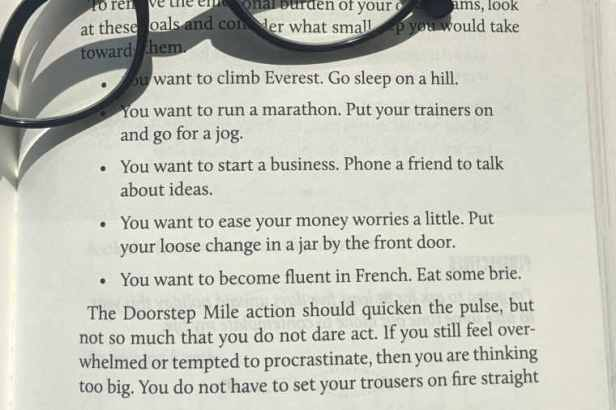 Close up image of bulletpoint list from paperback book The Doorstep Mile with glasses in corner