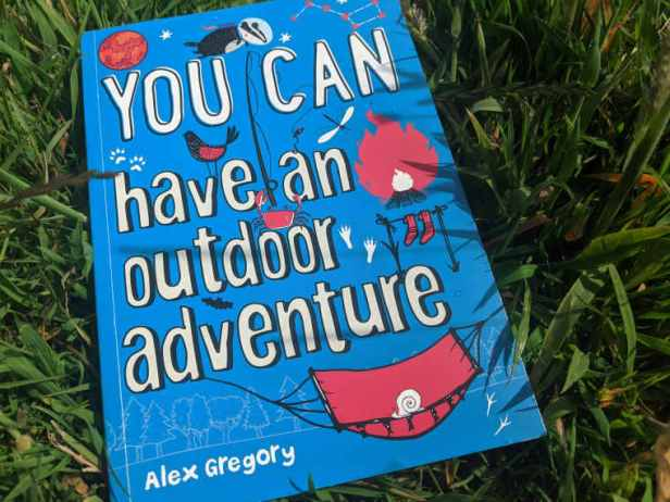 Blue book lying in grass title You Can Have an Outdoor Adventure by Alex Gregory