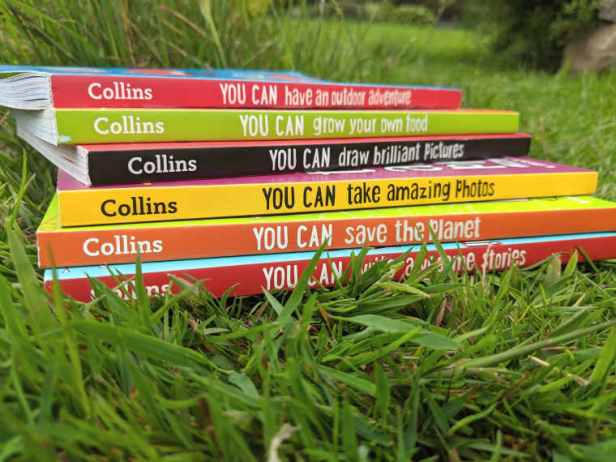 Close up of six brightly coloured books all entitled 'You Can' piled in grass