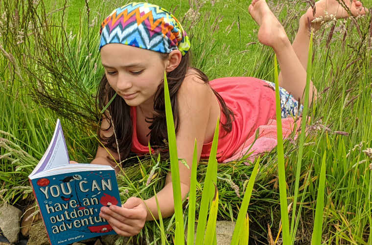 Girl in coloured clothing lying in long grass reading a blue book called You can have an outdoor adventure